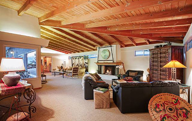 The resort-like feel continues in the living room. Looking out onto the patio and pool area, this huge L-shaped room, with its vaulted, natural wood ceilings and centerpiece fireplace, is the perfect place to spread out and unwind.