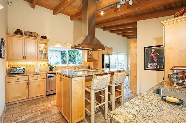Pancakes. It's vacation time and that's what I smell. This gourmet kitchen with its stone flooring, beamed ceiling and center-island stove, has a chalet vibe. And it makes me want pancakes. With Blueberries, thank you very much.