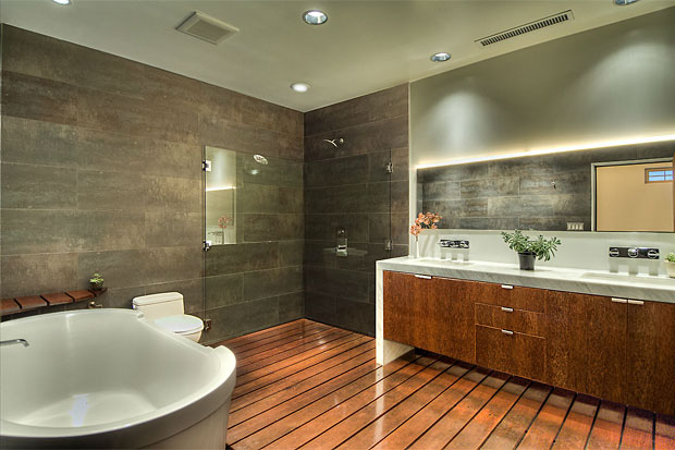 En suite, the ultra sexy bathroom has an oversized Philippe Starck soaking tub, a luxurious rainhead glass shower, warm Mangaris plank wood floors and Carrera Marble countertops, complete with designer sinks and fixtures.