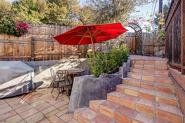 Outside, the tiled patio, which extends the living space of the home, is gated and private. And it's surrounded by beautiful, lush hillsides.