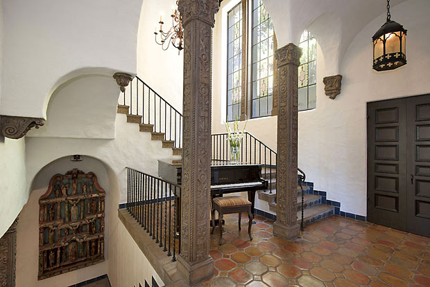 The entry spans two-stories with a staircase featuring original Spanish tiles, beautiful wrought iron railings and carved wood beams.