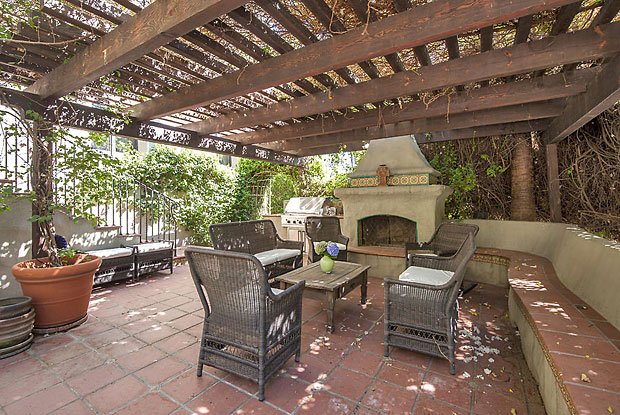The pergola covered patio near the entrance to the main house features a beautiful stone fireplace, gas barbecue and lots of built in seating.