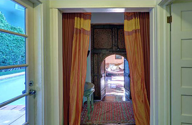 And here is a peek down the hall toward a door that leads to the next cool room of this house. The beautiful Moorish details around the doorway are a hint of the fun to come.