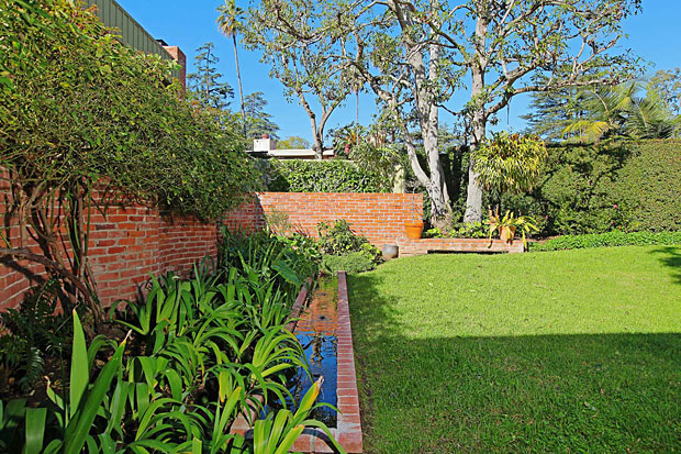 Neutra separated the front and rear gardens with this elegantly curved brick wall and further brings it to life with a long rectangular water feature.