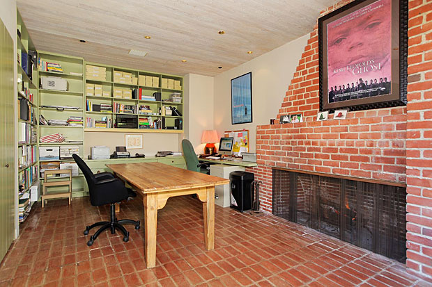 This office with two walls of built-ins, a large brick fireplace and brick floor, and an entire wall opening up to the outside is a perfect example of rustic colliding with modern. And doing so beautifully.