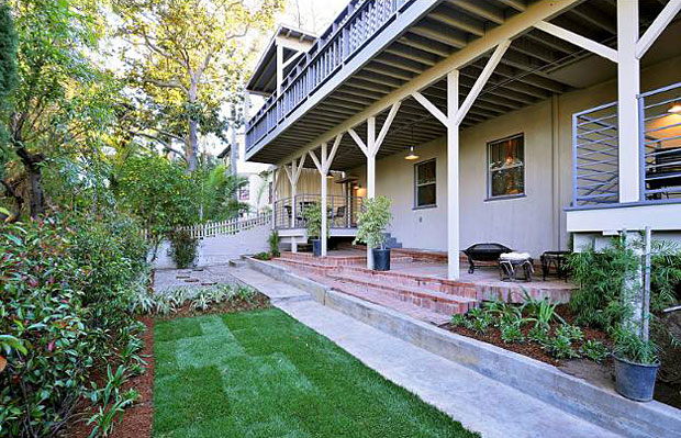 Beneath the shelter of the second floor deck is a large shaded patio area, which steps down to a private grassy yard.