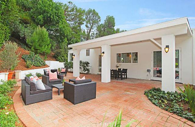 Dramatic tall French doors open to expansive patio space, perfect for entertaining and Angeleno living. Thanks to its perch on a slight elevation and tall hedges along one side of the property, the home enjoys a high degree of privacy.