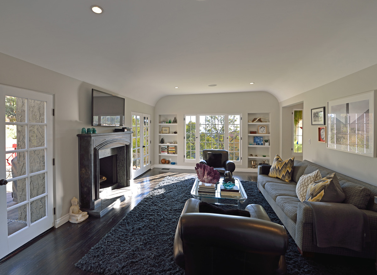 The living room features a coved ceiling and a fireplace flanked by French doors that open to spacious professionally landscaped grounds with a sparkling new pool and spa.