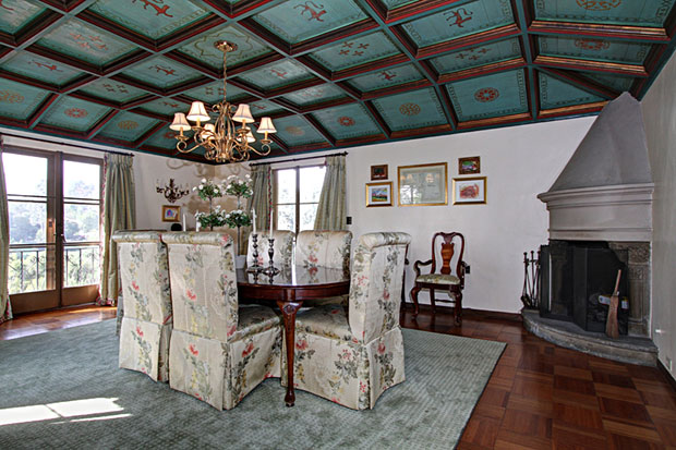 The formal dining room boasts a fireplace and an elaborate wood-beamed and hand-painted stenciled ceiling, which is truly unique..