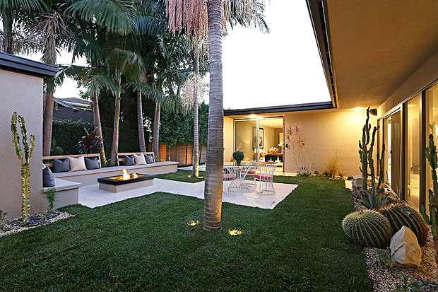 The upper level surrounds a private center garden landscaped with grasses and succulents, built-in concrete sofa and glass filled fire pit.