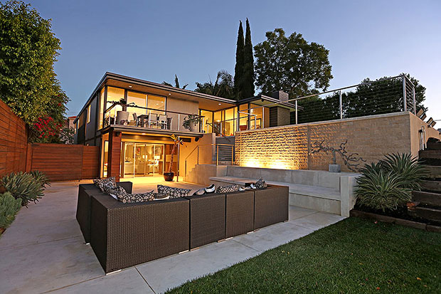 The lower level opens up to a large enclosed patio with built-in seating and a stacked stone wall fountain.