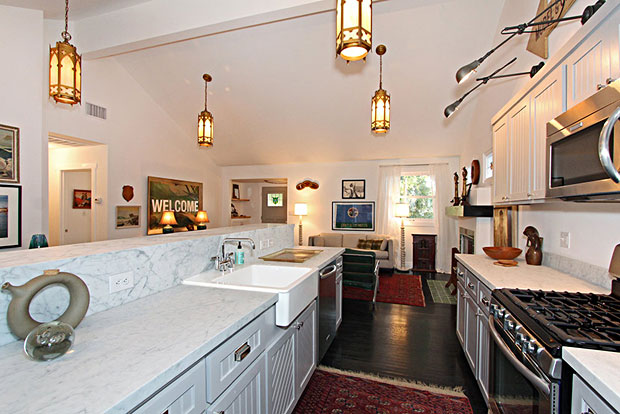 The kitchen has a farmhouse meets contemporary feel to it and features an apron sink, Carrara marble, stainless appliances and custom cabinetry.