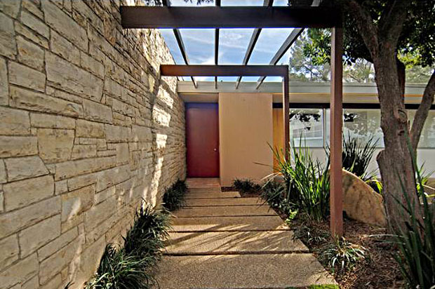 The home is situated at the end of a long driveway behind gates. The walkway to front door is accented by the architectural beam embellishments common to so many of Neutra's homes, allowing you to begin experiencing the feel of the home before you even enter.
