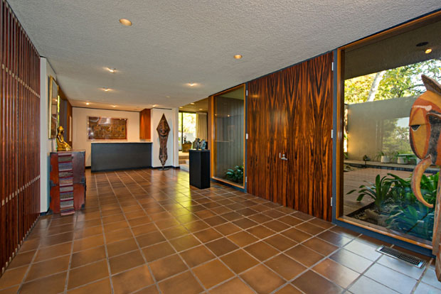 Two huge wood doors with with matching grain set up the entry into a massive tiled foyer.