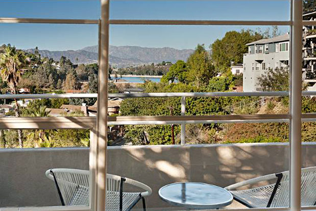The dramatic views of the Silver Lake Reservoir and the mountains beyond are visible from the main living spaces.