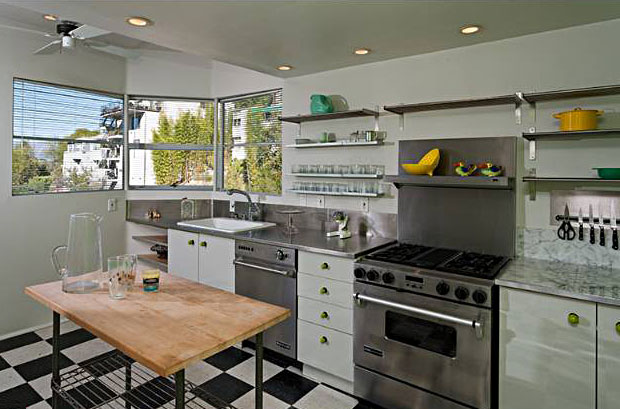 The kitchen is nicely updated and yet retains a vintage style, highlighted by the black white and white checkered linoleum and the windows that wrap around the one corner.
