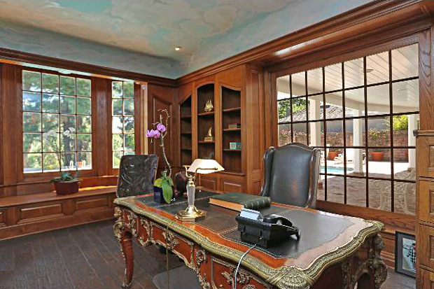 he office features large windows looking out to the backyard pool and patio area.