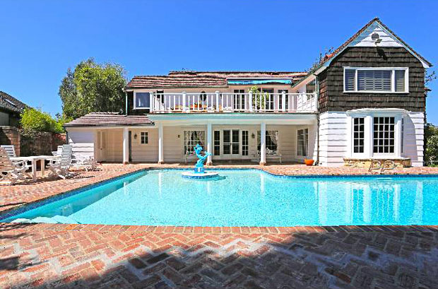 The stone and wood shingle exterior are timeless and work perfectly with the brick patio surrounding the large swimming pool in the back yard.