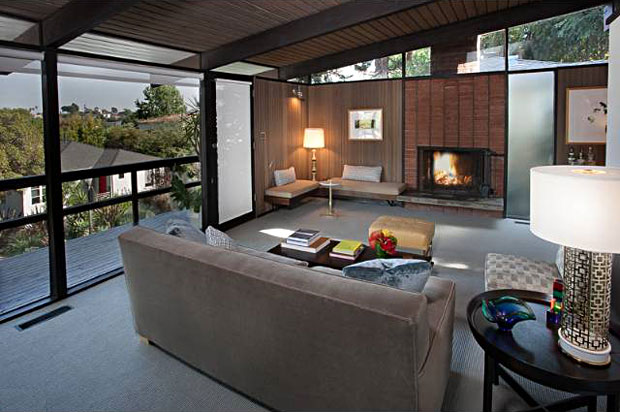 I love the built-in shelf seating by the fireplace. Outside the sliding glass door is a deck that skirts he front of the home providing tree-top views of the hillsides.