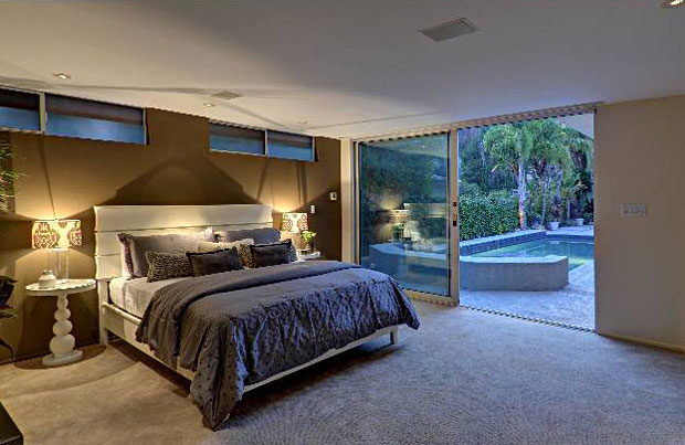 The master bedroom features transom windows and direct access to the hot tub and pool.
