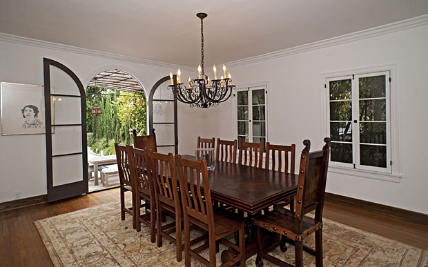 The dining room is graced by arched oversized doors that lead to the pool area.