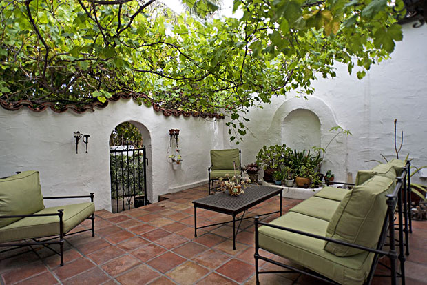 Relax with a glass of wine on this small private patio featuring mature grape vines that provide shade and fruit.