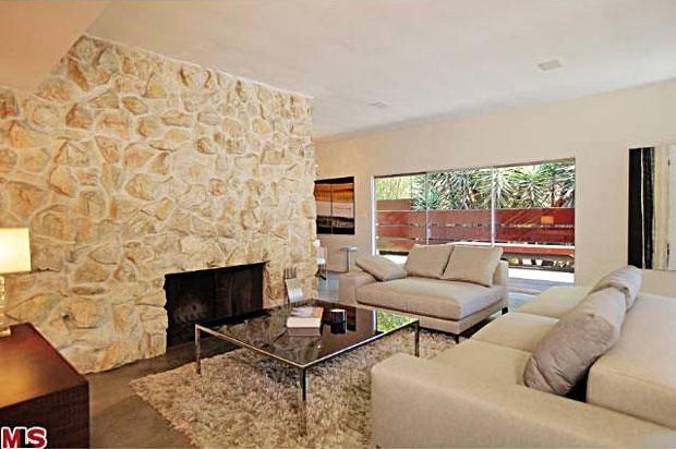 The living room has an appealing mix of new and original touches throughout, including a fireplace that's set within a full wall of stone.