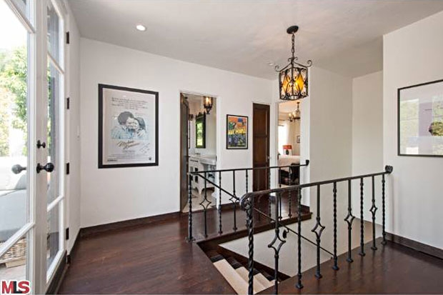 The hallway fixtures and wrought iron railings stay true to the home's original style.