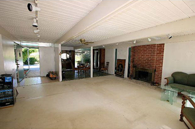 The living is spacious and features a fireplace that will likely stick around through renovation.