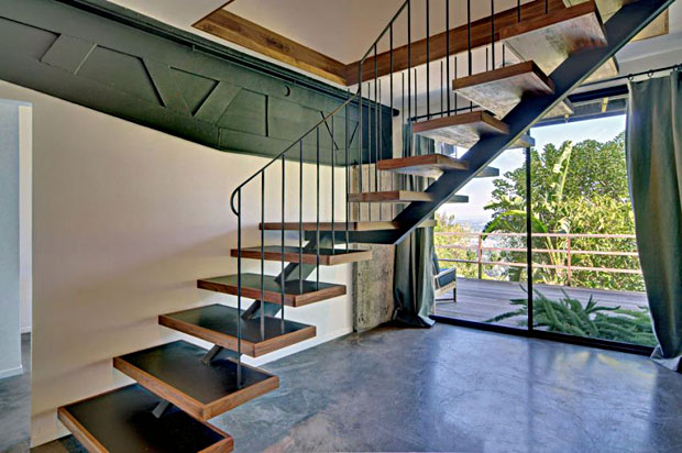 As you walk down the custom, walnut and iron floating stairs to the lower level you immediately notice the exposed trusses, which are an awesome feature.