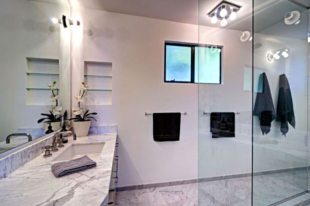 Stunning marble covers the bathroom walls.
