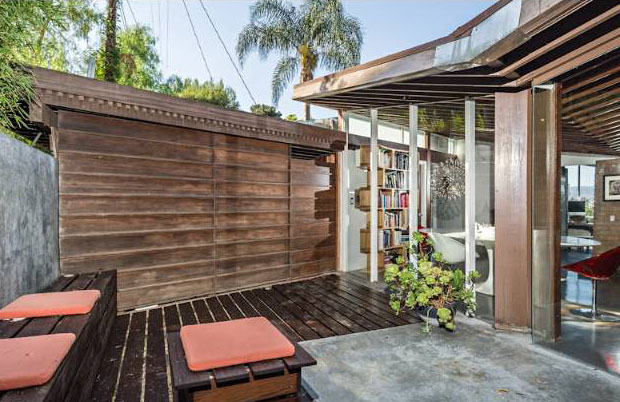 Private patio with walls of cement and beautiful wood walls.