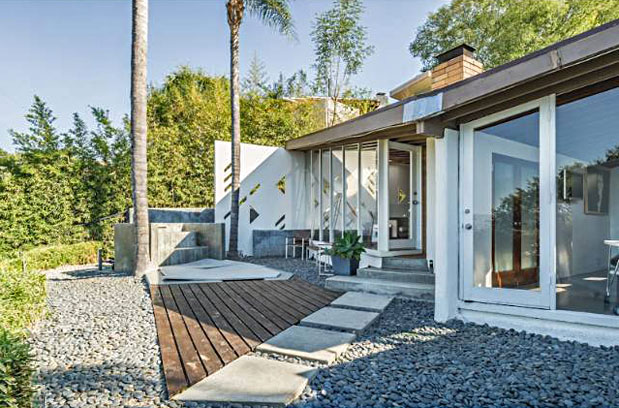 The exterior has clean lines, large windows, and check out the geometric cut-outs in the privacy wall.