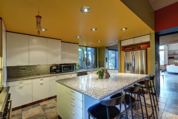 The kitchen has clean lines with granite counter tops and tile floors.