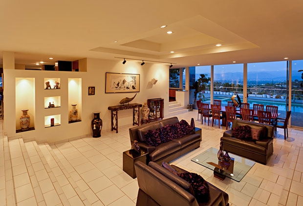 Walk down into a glistening living room that opens up into the backyard and pool area.