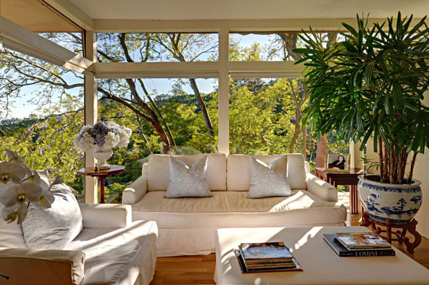 The home is enveloped by greenery., yet plenty o' sunlight and views are to be enjoyed in the den...