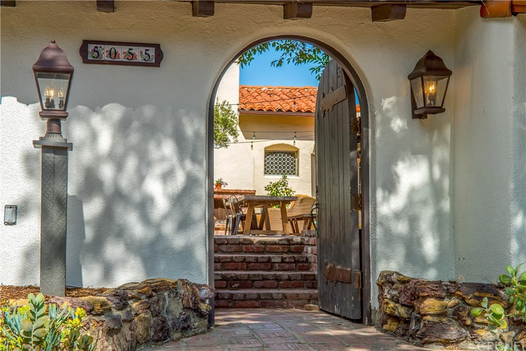 Before even opening the gate that leads to the courtyard, you can tell that great things await.  Even at this starting  point, everything is pretty fantastic: the tile house numbers, the gas lantern style lamps,   and  the door itself is with its large, steel structural braces is beautiful.