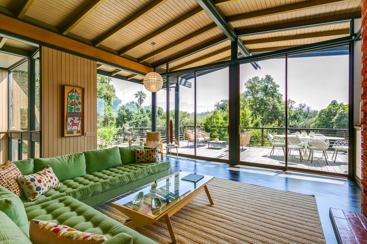 The glass-walled living room leads to decks, which overlook the pool. And beyond that, you can take in the views of the Arroyo and the San Gabriel Mountains.