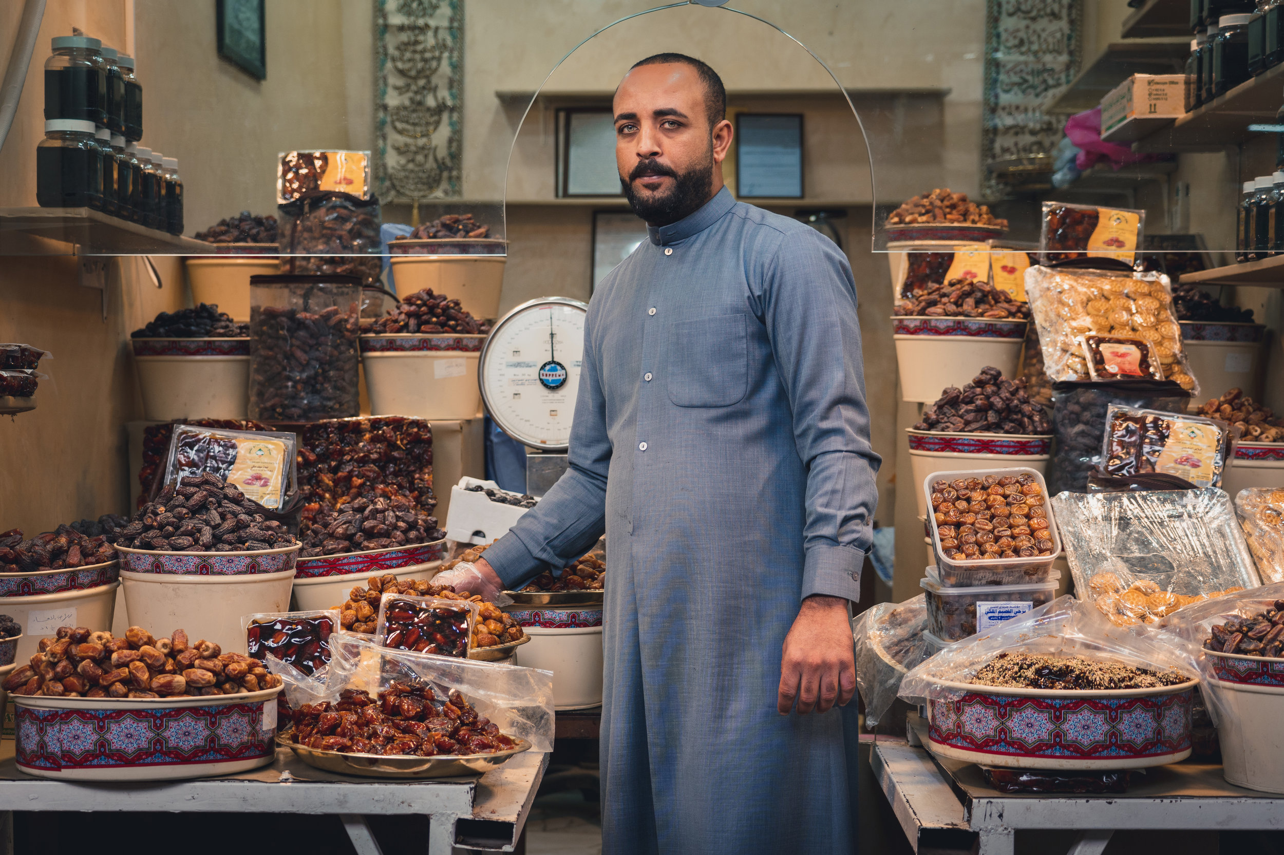 I took this photo in Kuwait City at the Souq Al-Mubarakiya, a local market that has been around for at least 200 years in Kuwait. There one can buy all kinds of locally grown or prepared foods, perfumes, clothing, and jewelry. This mans shop was all about dates, which are grown throughout the Middle East and are a main ingredient in many of the desserts. I was walking around the souq with my fellow crewmember, also a photographer, and as we passed by this man, he insisted on us trying all of the different types of dates he had available.