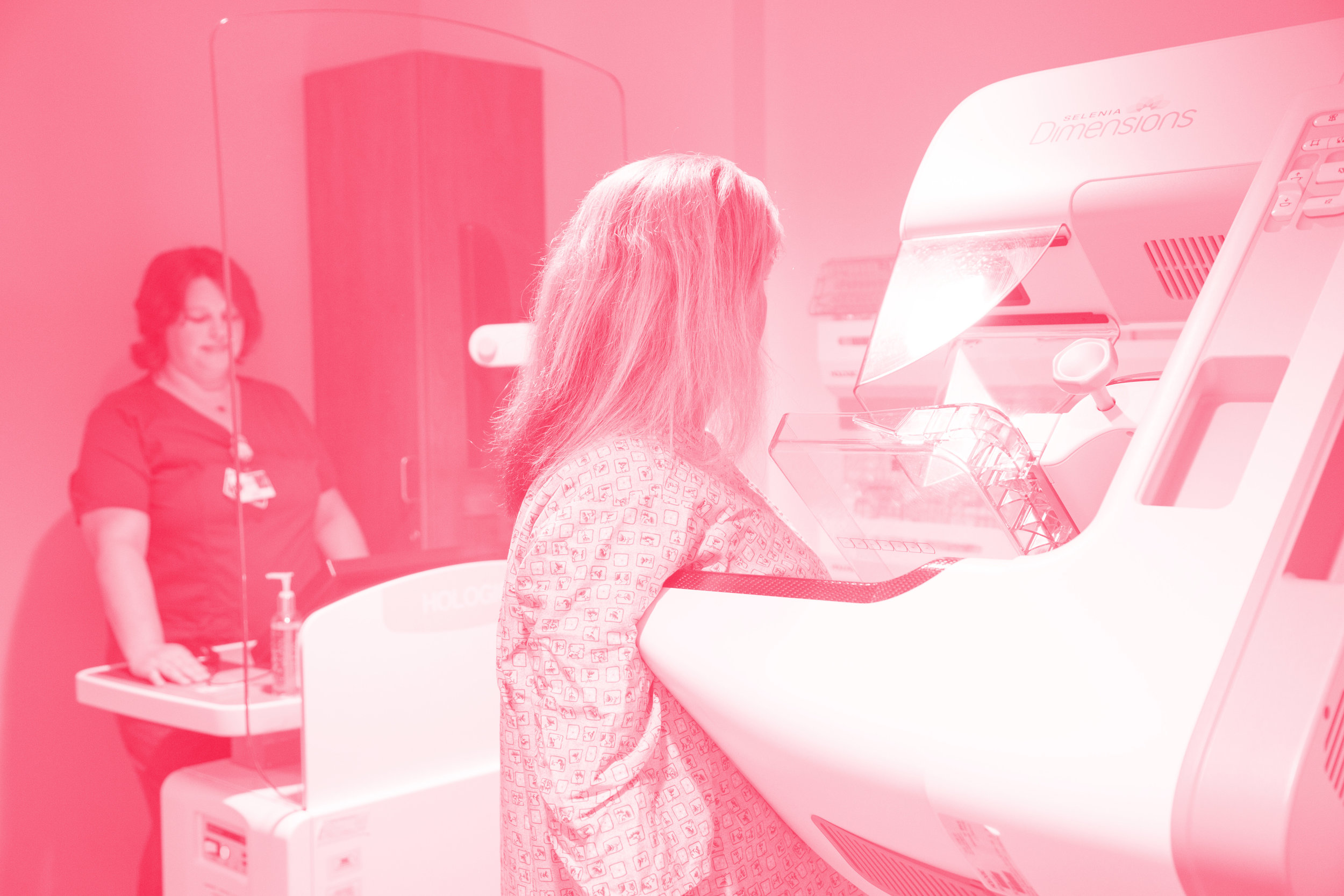Radiology tech performs mammography scan on patient