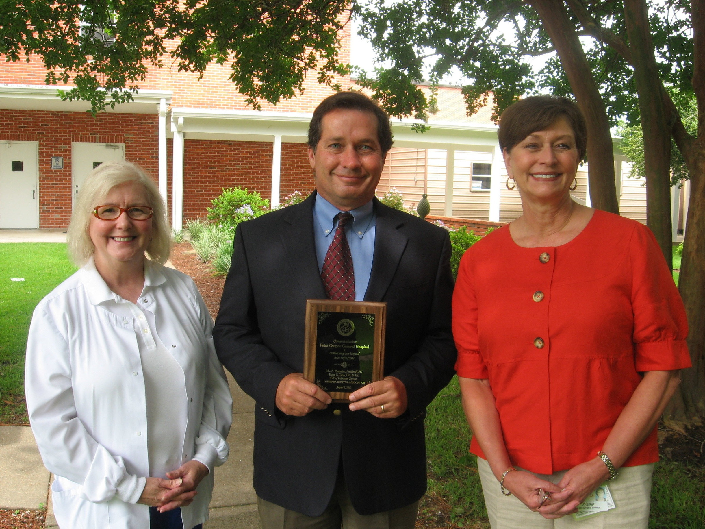 Maggie Jarreau (left), Chad Olinde, and Elaine Hurme display PCGH's NRHA award for performing in the top 20 of critical access hospitals.