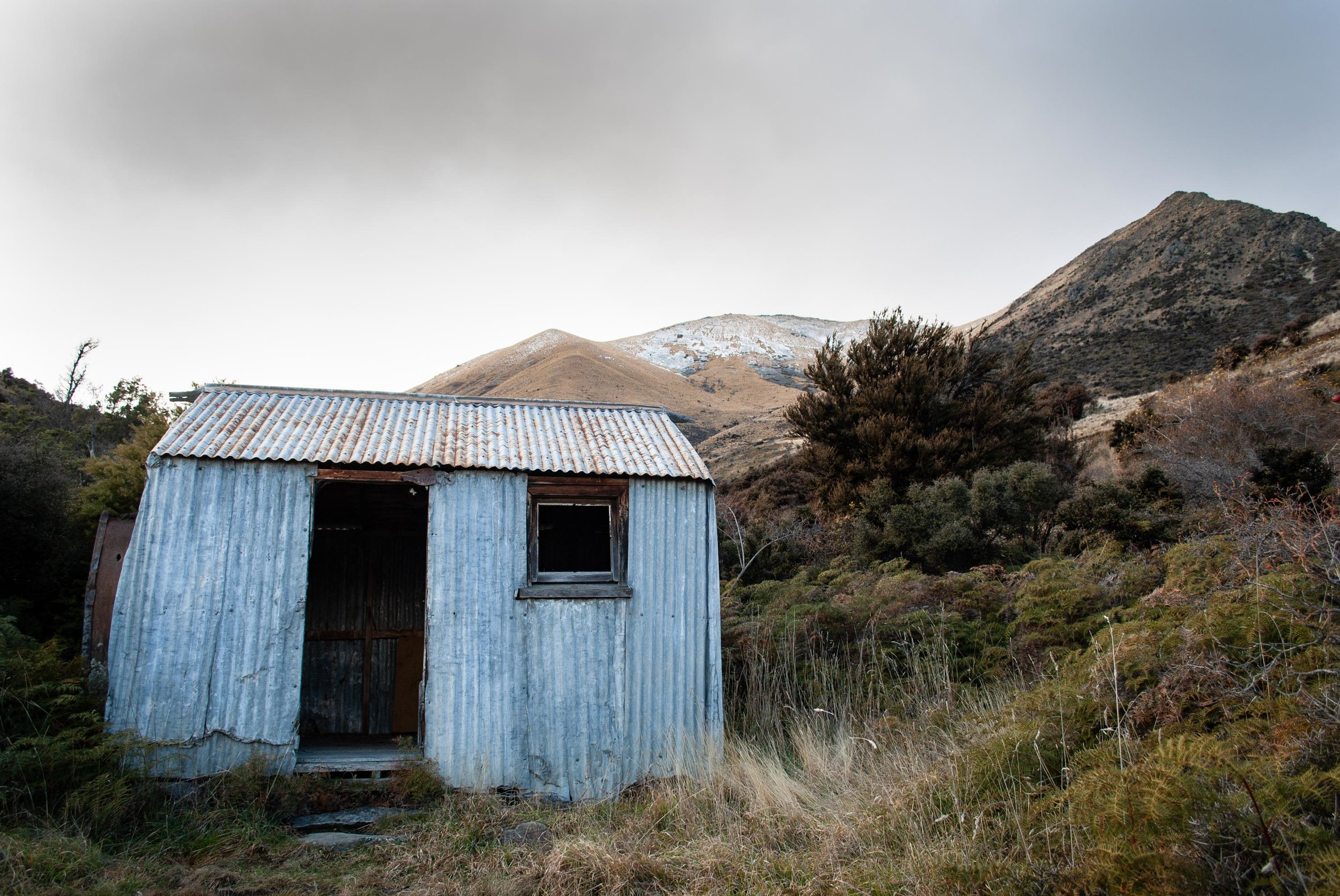 The old Greta Hut on the way to climb the Ben Ohau range shown in the distance.