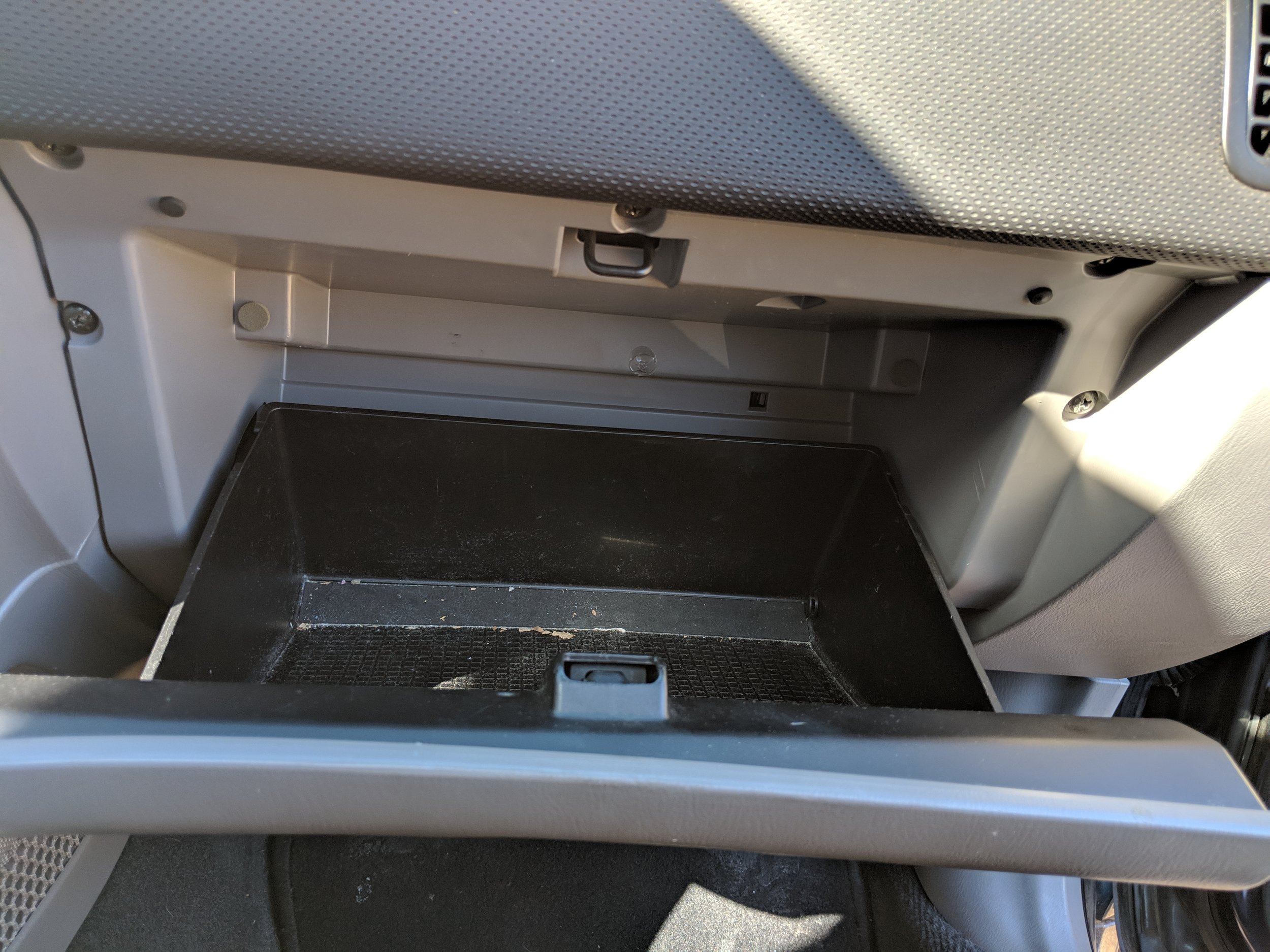 Open wide! Surrounding the inside of the glove box are three screws along the top and two on the side.