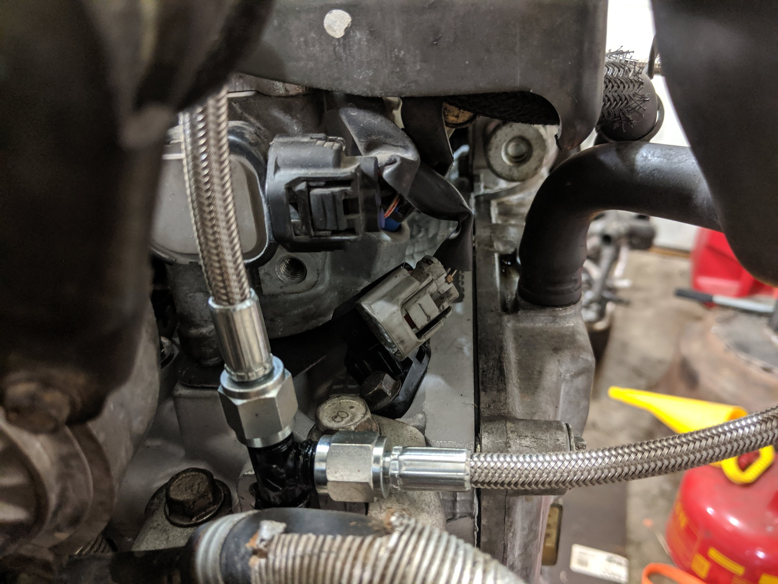 With the engine out of the car this cam sensor on the passenger side is easy to see. When it is in the engine bay reaching towards the back of the head you will find it.