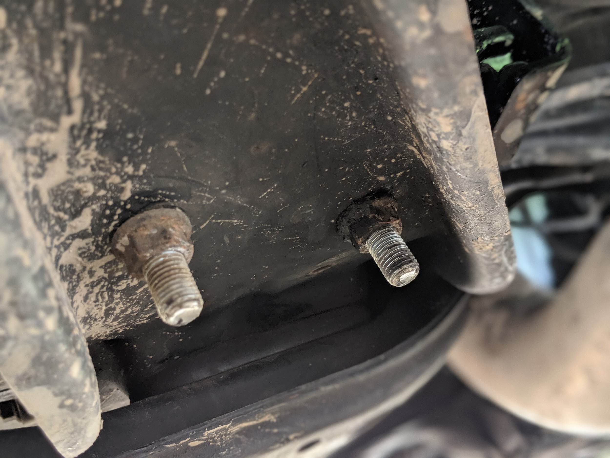 These two nuts hold the transmission mount to the bracing. With them removed the brace will slide on down.