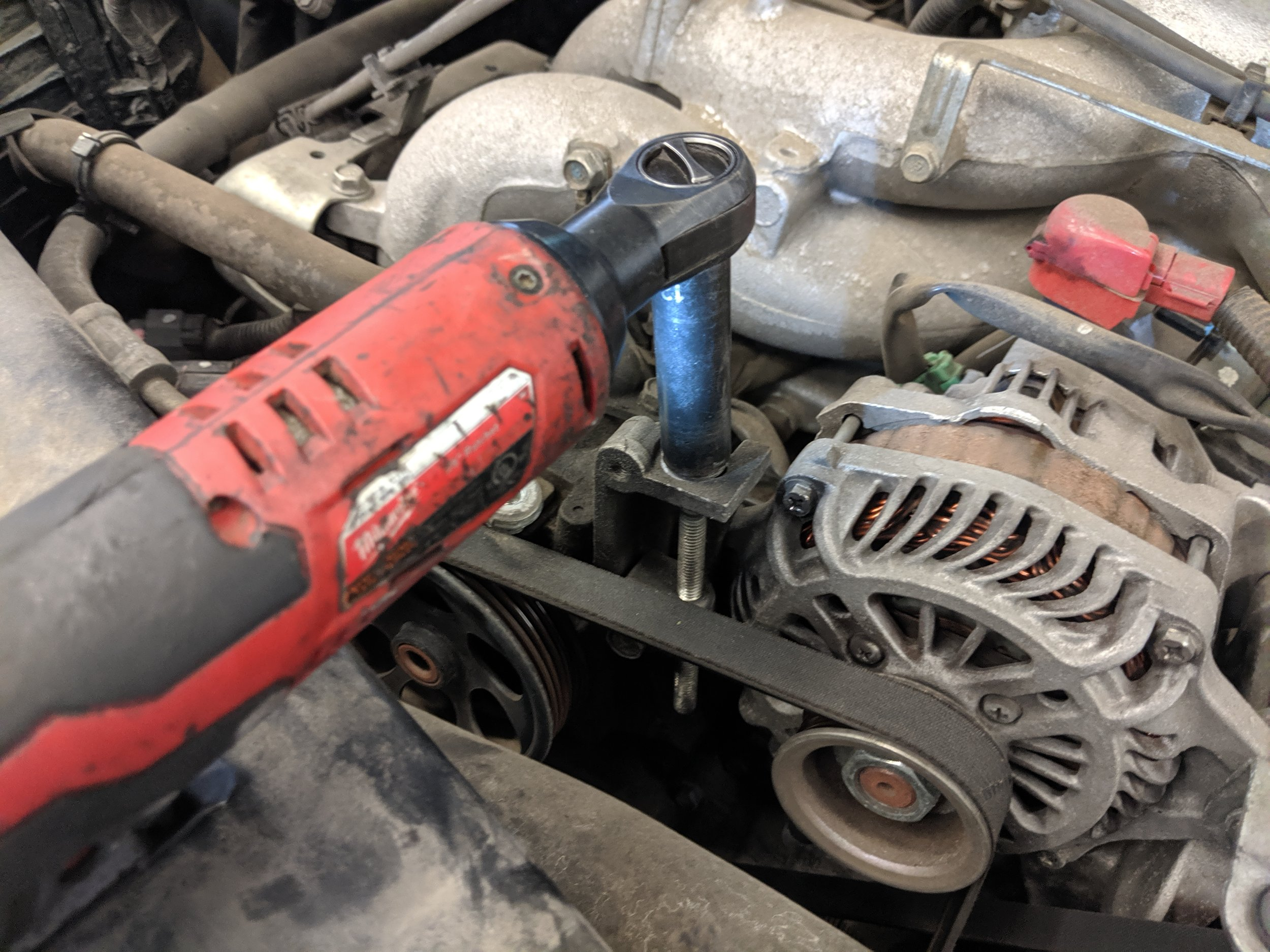 Spinning this bolt out will release the tension from the belt and allow the alternator to sink. This makes removal of the belt possible.  Milwaukee Electric 3/8 ratchet