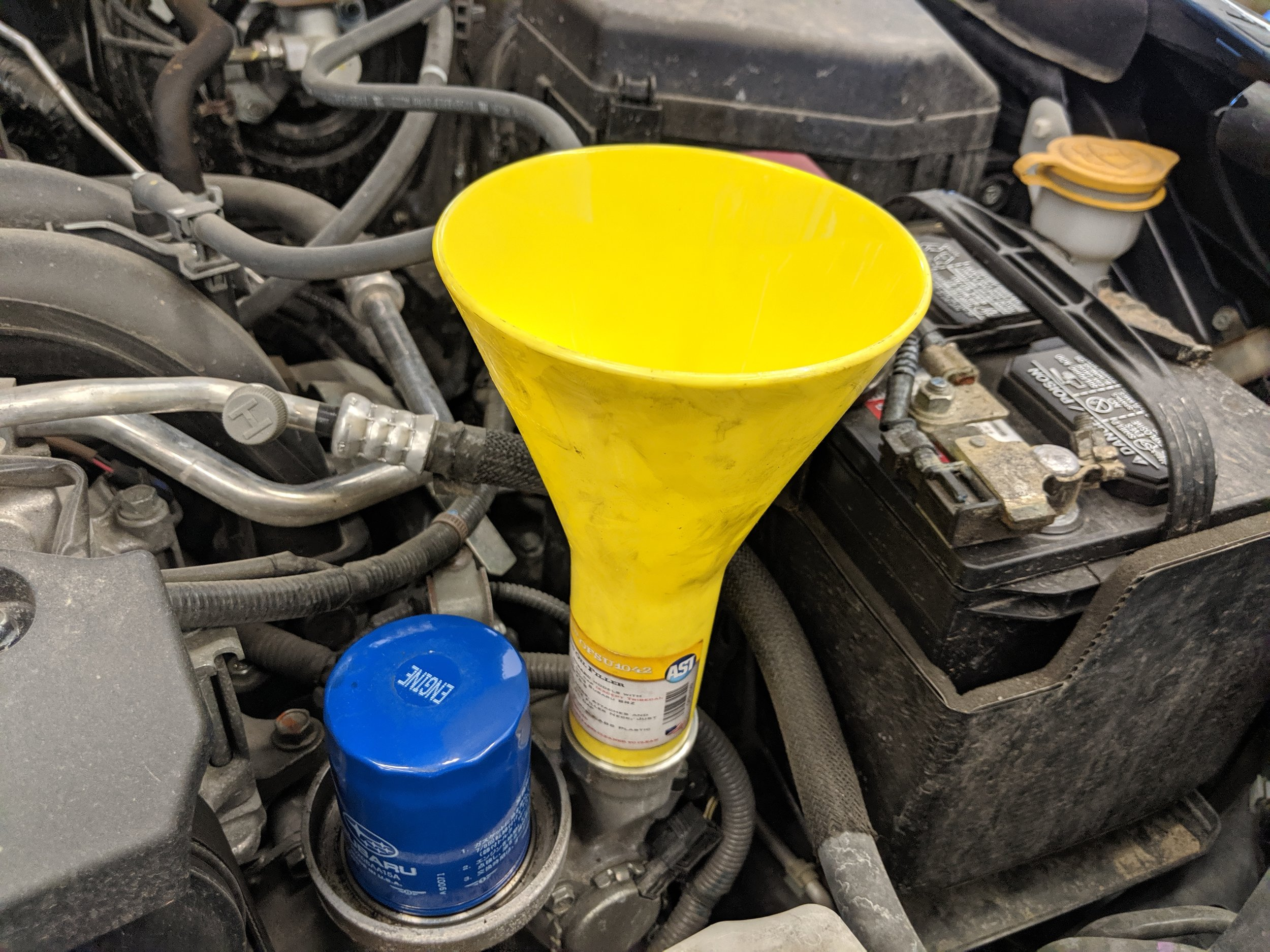 The Assenmacher oil funnel screws right into most Subaru oil fill necks. It allows you to pour that oil quite a bit faster without worrying about spills. Shown on a FA engine.