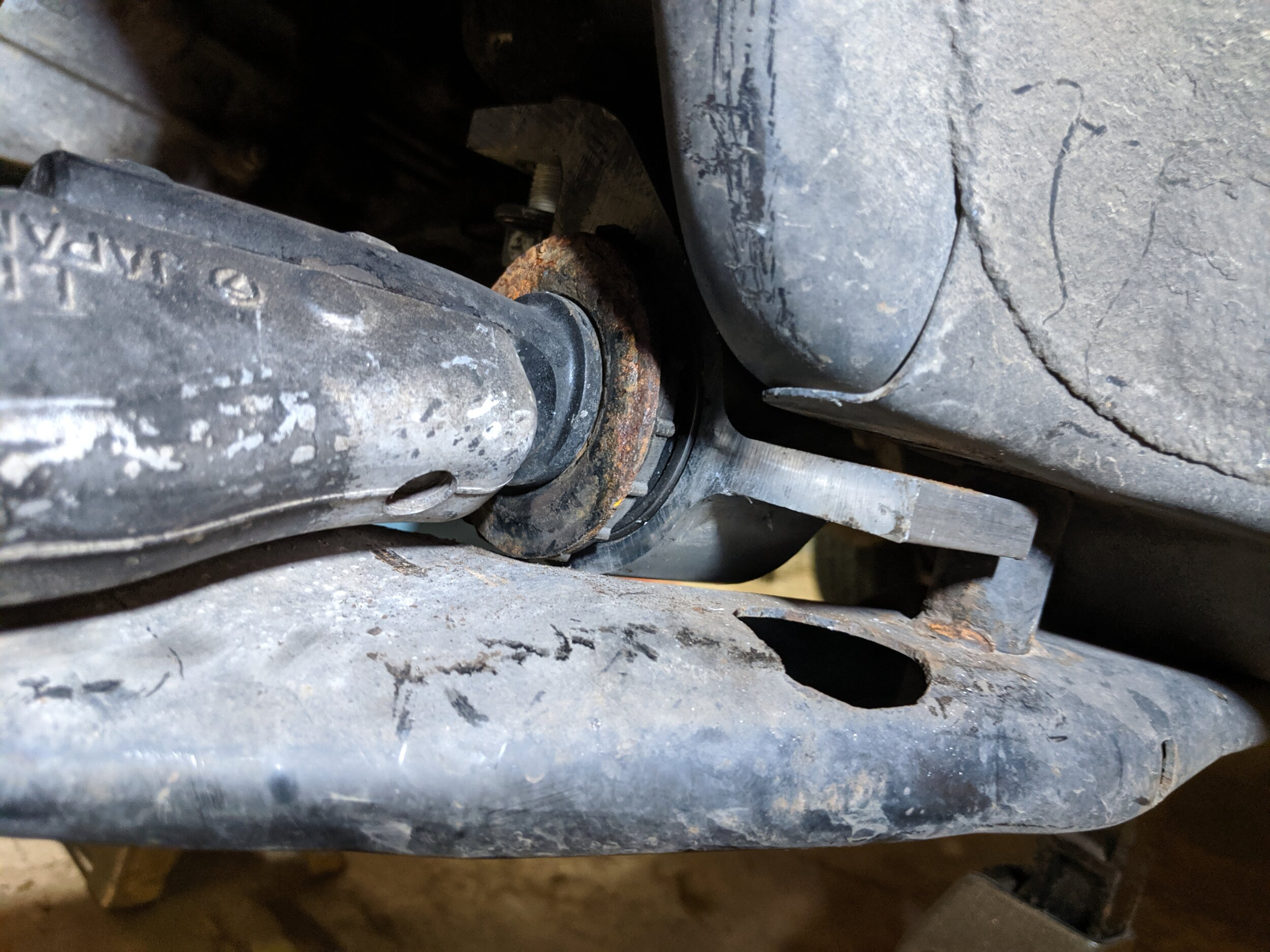 If you leave the subframe on this is what you will need to do. One bolt removed and one very loose to allow the mount to be shifted and allow for the arm to come out.