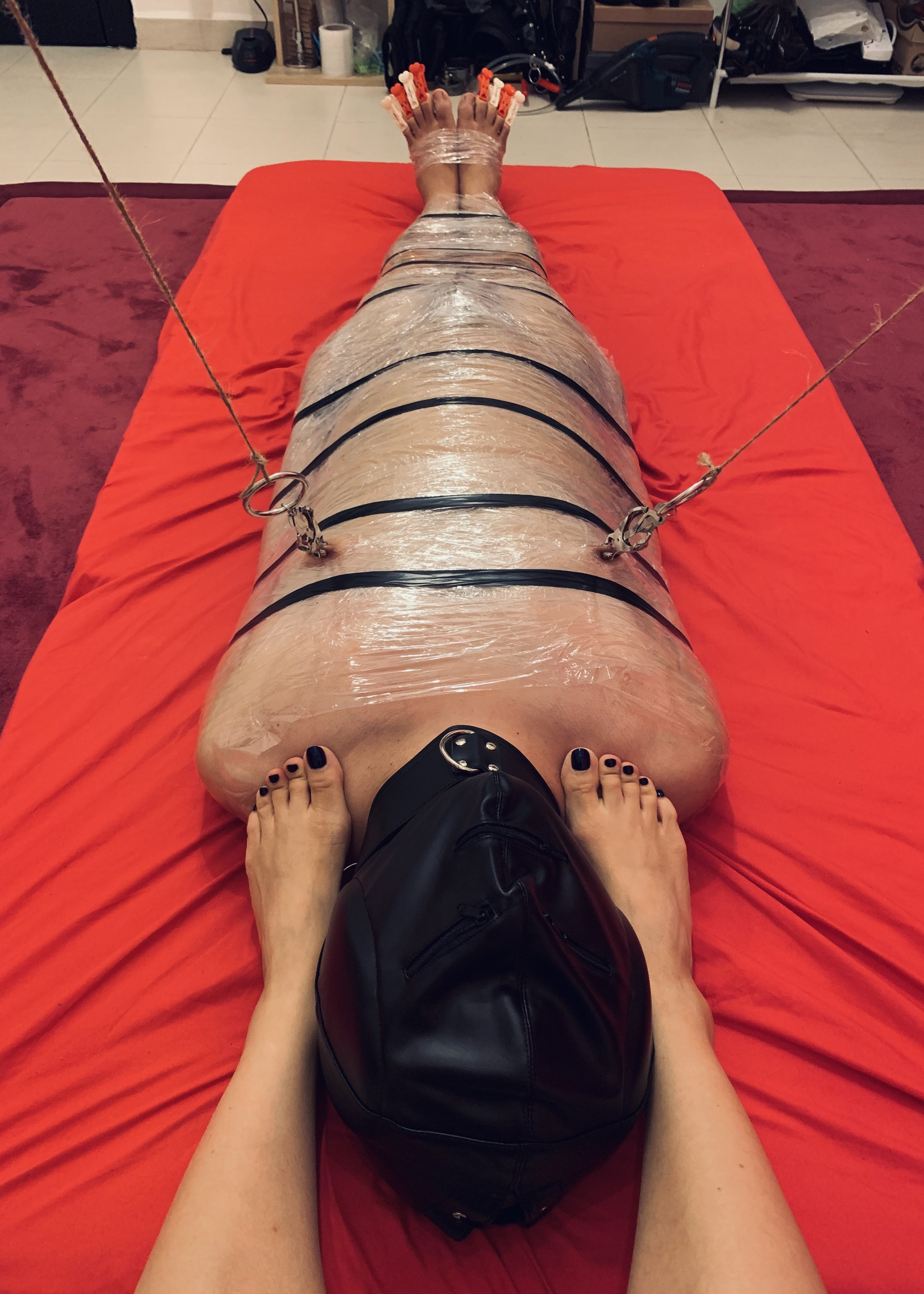 C is mummified in saran wrap, and is sporting a full head padded hood, nipple clamps pulled taut and pegs on his toes. What a champion!