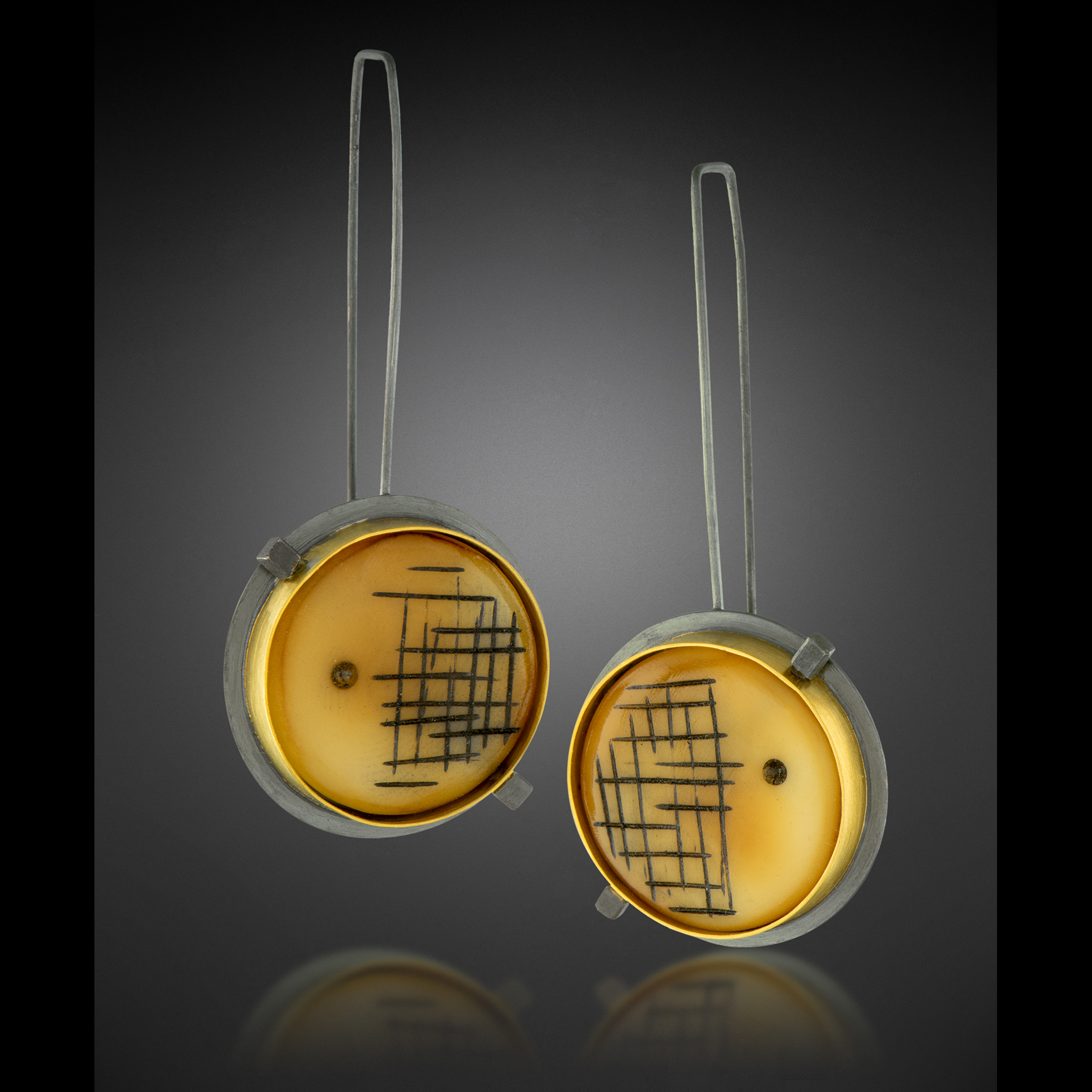 Tagua earrings set in oxidized sterling silver with 22k gold bezels. Please inquire about price and availability.